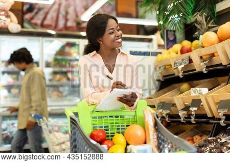 Cheerful African Woman Doing Grocery Shopping With List In Supermarket
