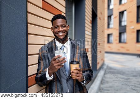 Handsome Black Businessman In Coat With Coffee To Go And Smartphone Standing Next To Office Building