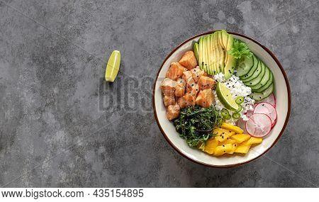 Salmon Poke Bowl With Rice, Mango, Avocado, Seaweed, Radish, And Cucumber. Healthy Fast Food Concept
