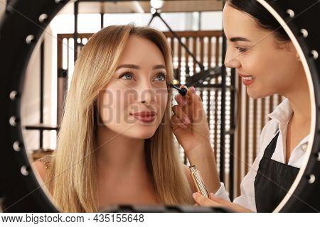 Professional Makeup Artist Applying Mascara Onto Woman's Eyelashes In Salon, View Through Ring Lamp