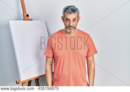 Handsome middle age man with grey hair standing by painter easel stand skeptic and nervous, frowning upset because of problem. negative person.