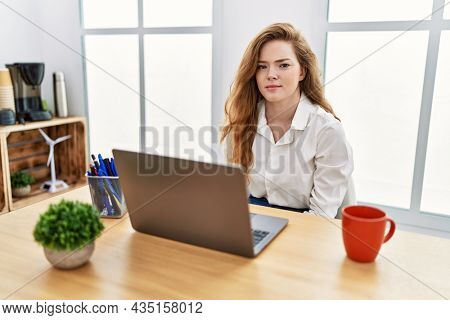 Young caucasian woman working at the office using computer laptop skeptic and nervous, frowning upset because of problem. negative person.