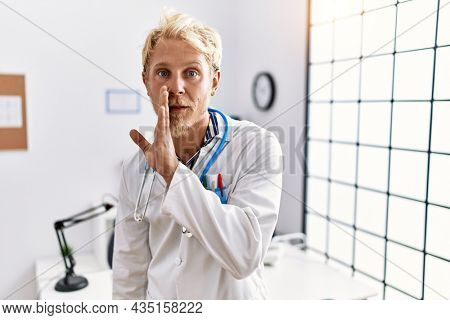 Young blond man wearing doctor uniform and stethoscope at clinic hand on mouth telling secret rumor, whispering malicious talk conversation