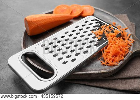 Grater And Fresh Ripe Carrot On Grey Table, Closeup