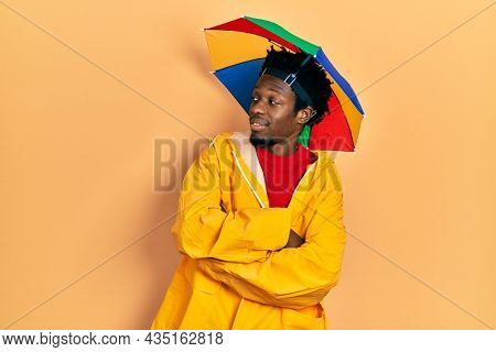 Young african american man wearing yellow raincoat looking to the side with arms crossed convinced and confident