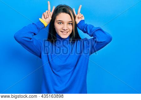 Young brunette girl wearing turtleneck sweater posing funny and crazy with fingers on head as bunny ears, smiling cheerful
