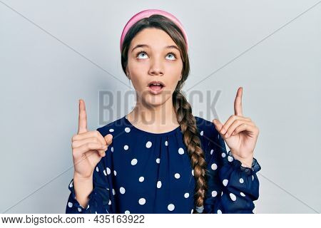 Young brunette girl wearing elegant look amazed and surprised looking up and pointing with fingers and raised arms.