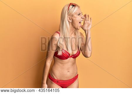 Young blonde woman wearing bikini shouting and screaming loud to side with hand on mouth. communication concept.