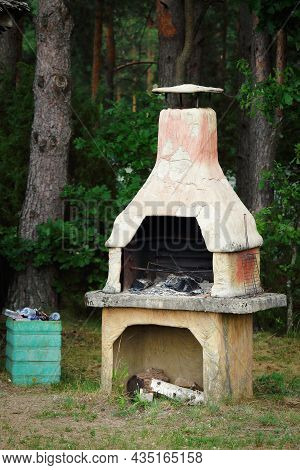 Old Clay Furnace With Logs Standing Outdoors Near The Forest And Full Garbage Bin