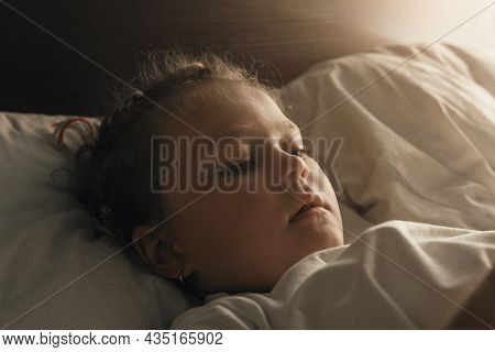 Portrait Of A Cute Adorable Little Girl Getting Ready For Bed While Lying In Her Bed.