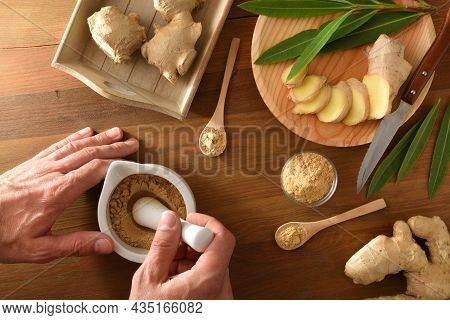 Hands Preparing  Ginger Powder For Curative And Culinary Purposes With Ginger Root Sliced In Portion