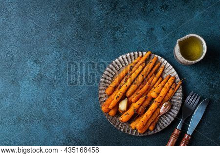 Roasted Carrots Ready To Eat. Glazed Carrot With Herbs And Garlic Top View. Fried Carrot On Dark Bac