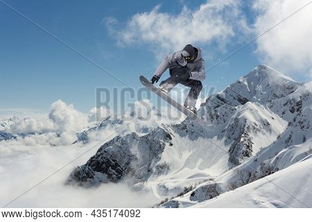 A jumping snowboarder in the mountains. Snowboarding, winter extreme sport.