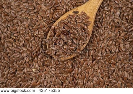 Close Up Of Brown Flax Seeds Background, Top View, Studio Shot. Brown Flax Seed On A Spoon. Linen Se