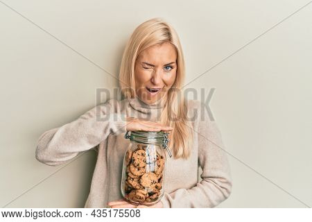 Young blonde woman holding jar with chocolate chips cookies winking looking at the camera with sexy expression, cheerful and happy face.