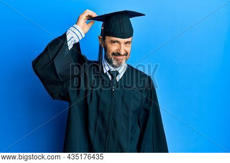 Middle age hispanic man wearing graduation cap and ceremony robe confuse and wonder about question. uncertain with doubt, thinking with hand on head. pensive concept.