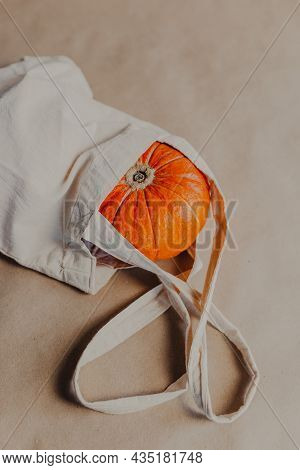 Orange Pumpkin In Beige Shopper On Paper Background. Halloween Pumpkin Inside Beige Bag.
