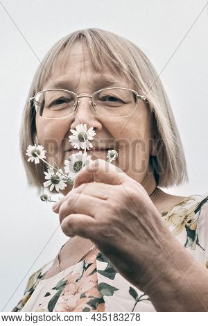 Portrait Of An Elderly Woman Holding A Bouquet Of Flowers, Smelling The Scent Of Daisies. Autumn.