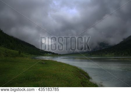 The Ak-kem River Flows In A Mountain Valley, Grass Grows On The Banks Of The River, There Are Many T
