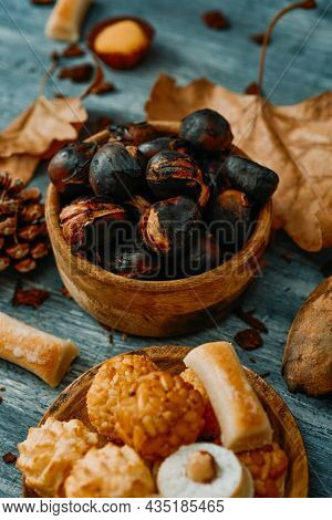 closeup of a plate with some different confections eaten in Spain on All Saints Day, such as assorted Panellets or Huesos de Santo, on a table next to a bowl with some roasted chestnuts