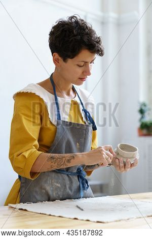 Young Creative Potter Woman In Apron In Studio Use Tools For Raw Kitchenware Decoration Before Bakin