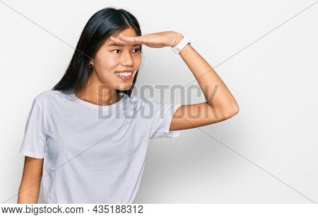 Beautiful young asian woman wearing casual white t shirt very happy and smiling looking far away with hand over head. searching concept.