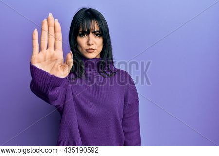 Young brunette woman with bangs wearing turtleneck sweater doing stop sing with palm of the hand. warning expression with negative and serious gesture on the face.