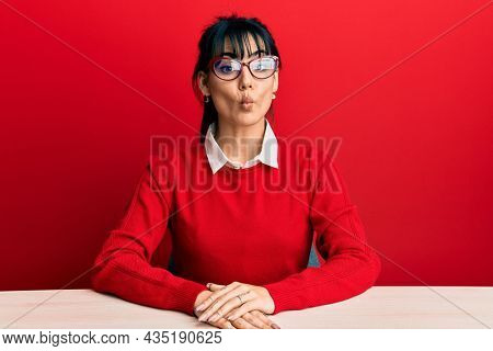 Young brunette woman with bangs wearing glasses sitting on the table making fish face with lips, crazy and comical gesture. funny expression.