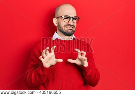 Young bald man wearing casual clothes and glasses disgusted expression, displeased and fearful doing disgust face because aversion reaction. with hands raised