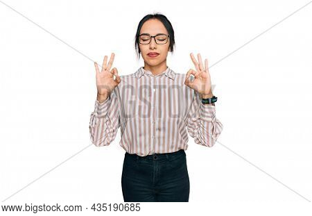 Young hispanic girl wearing casual clothes and glasses relaxed and smiling with eyes closed doing meditation gesture with fingers. yoga concept.