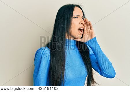 Young hispanic girl wearing casual clothes shouting and screaming loud to side with hand on mouth. communication concept.