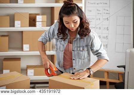 Concentrated Young Asian Postal Worker With Curly Hair Using Duct Tape While Packing Parcels