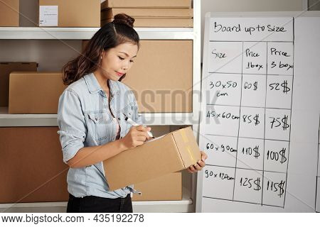 Serious Young Asian Postal Worker Standing Against Shelves With Packages And Signing Parcel Box