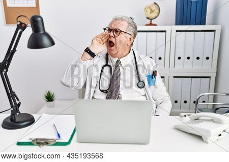 Senior caucasian man wearing doctor uniform and stethoscope at the clinic shouting and screaming loud to side with hand on mouth. communication concept.