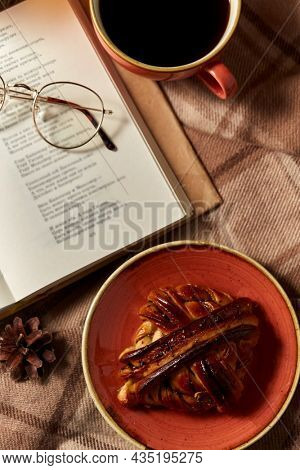 hygge, season and leisure concept - open book of poems with glasses, cup of coffee and cinnamon bun on ceramic plate on warm blankets at home