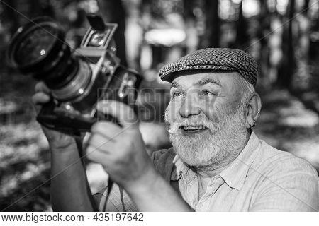 Old Camera Man Summer Outdoor. Active Senior Man Make Photo Of Nature. Photographer Man Holding Retr