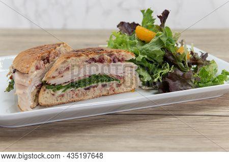 Turkey Panini Sandwich Showing Layers Of Provalone, Bacon, Mozzarella, And Arugula Served With A Sal