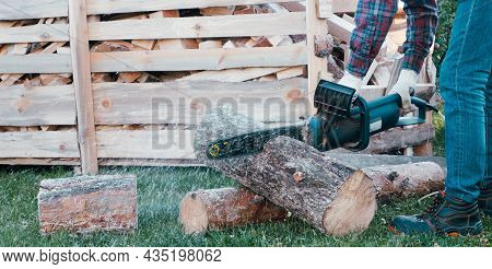 Close-up Of Woodcutter Sawing Chain Saw. Chainsaw Bar And Cutt. Woodcutter Saws Tree With Chainsaw O