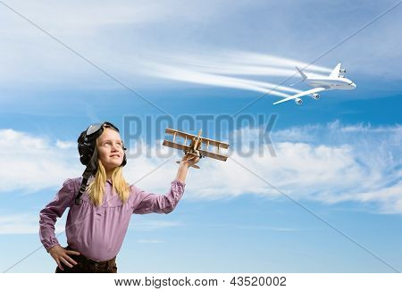 girl in helmet pilot playing with a toy airplane