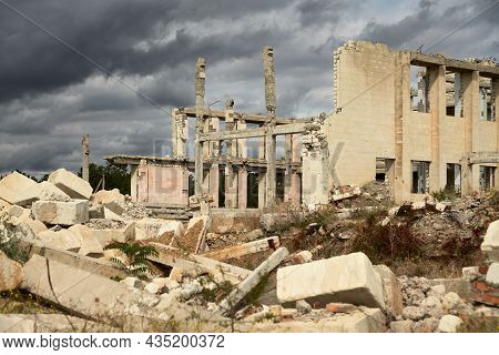 A Ruined Building Without A Roof With Dismantled Walls. Fragments Of Building Structures Lie In Fron