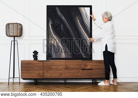 Senior woman adjusting an aesthetic photo frame on a wooden cabinet in a Japandi living room