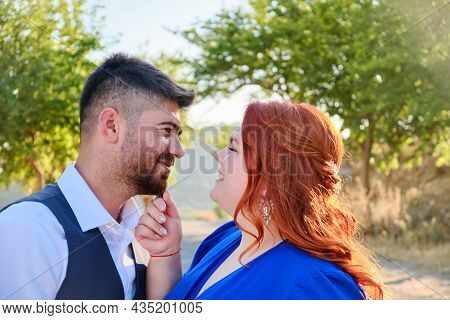 Gorgeous Happy Caucasian Plus Size Red Headed Woman Touches Her Husband Smiling. Mixed Race Couple E