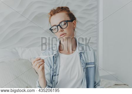 Young Unhealthy Red-haired Lady Holding Thermometer While Sitting On Bed At Home, Feeling Sick, Suff