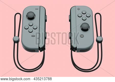 Portable Black Video Game Controllers On The Rope On Pink Background
