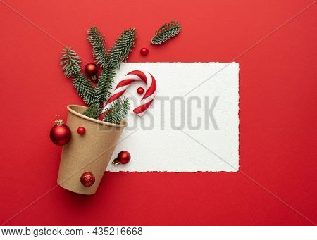 Christmas card with frame on red background and Christmas decorations. Flat lay, top view and copy space for text