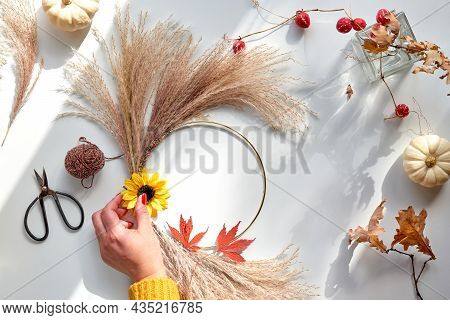 Hands Making Dried Floral Wreath From Dry Pampas Grass And Autumn Leaves. Hands In Sweater With Mani