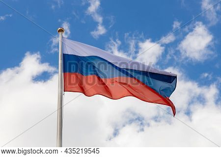 The Flag Of Russia Flutters In The Wind On A Sunny Day. Flag Of The Russian Federation On A Pole Aga