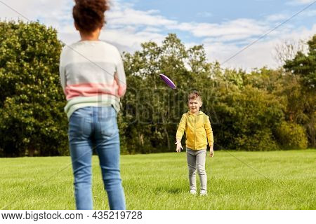 childhood, leisure and people concept - happy children playing game with flying disc at park