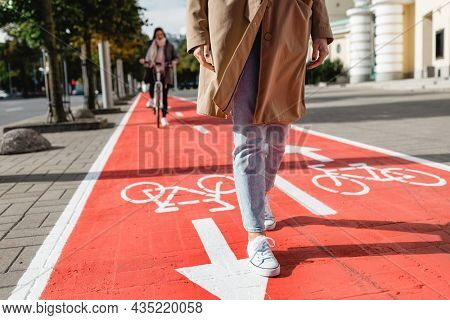 people, city and traffic concept - close up of woman's feet walking along separate bike lane or red road with signs only for bicycles on street