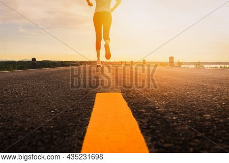 Athlete Running On The Road Trail In Sunset Training For Marathon And Fitness. Motion Blur Of Woman